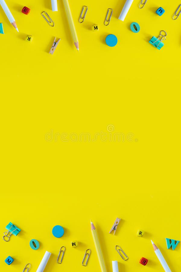 Mångfärgade skolatillförsel på gul bakgrund med kopieringsutrymme Vertikal lägenhet som är lekmanna- för sociala massmediaberätte royaltyfri fotografi