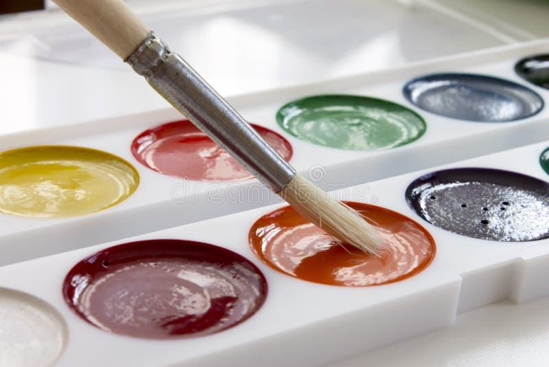 Mångfärgade vattenfärgmålarfärger och borste Design för kontors- och skolateckningskonst royaltyfria bilder
