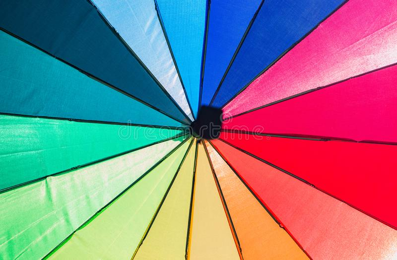 Mångfärgat paraply med det svarta handtaget arkivfoto