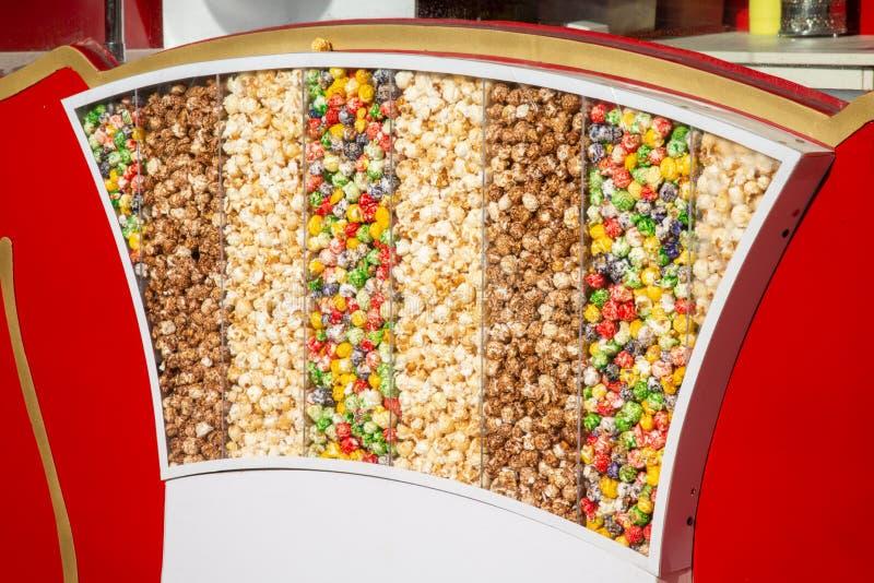 Mångfärgat sött popcorn är i en kugge under solen Bakgrund arkivbilder
