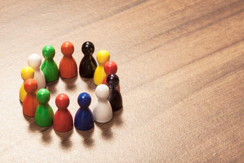 Mångfald vänner, cirkel, statyettbegrepp på den wood tabellen arkivbild