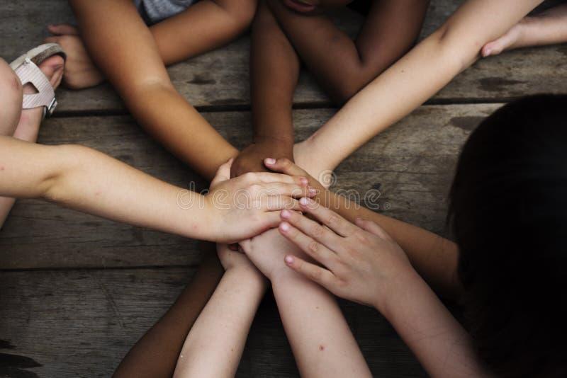 Mångfaldgrupp av ungar satta händer tillsammans royaltyfri fotografi