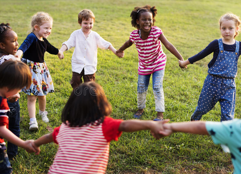 Mångfaldgrupp av ungar som rymmer händer i cirkel arkivfoto