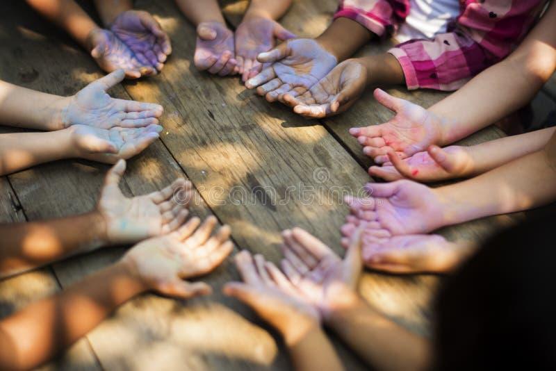 Mångfaldgrupp av ungar som rymmer händer i cirkelkrita fotografering för bildbyråer