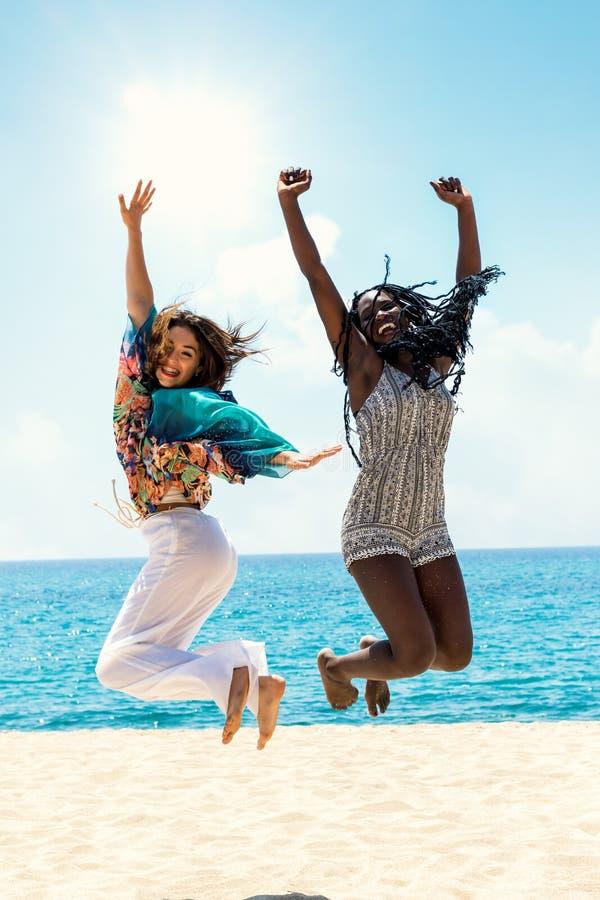 Mångfaldtonår som hoppar på stranden royaltyfria bilder