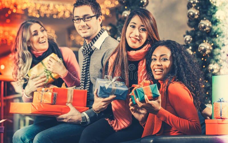 Mångfaldvänner med julklappar och påsar som shoppar i galleria royaltyfria foton