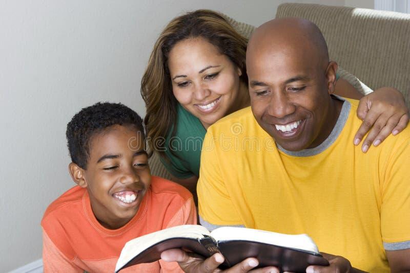 Mångkulturell familj för afrikansk amerikan som läser bibeln arkivfoto