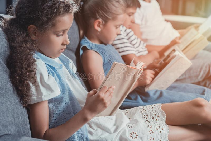 Mångkulturell grupp av fokuserade barnläseböcker, medan sitta på soffan royaltyfria bilder
