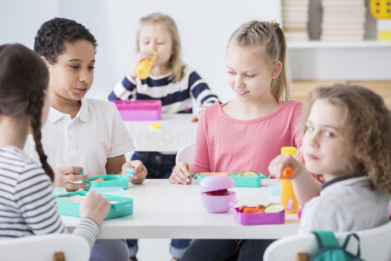 Mångkulturell grupp av ungar som äter lunch på skolan royaltyfri foto