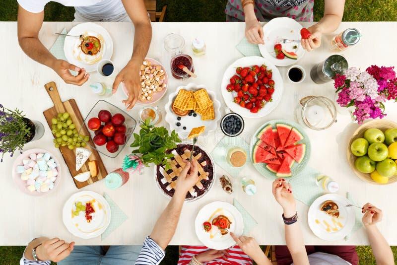 Mångkulturell grupp som utanför delar mat arkivfoton