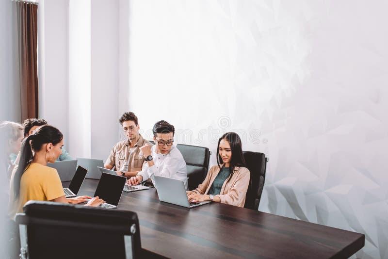 mångkulturella affärspartners som har möte på tabellen med bärbara datorer i modernt royaltyfri fotografi