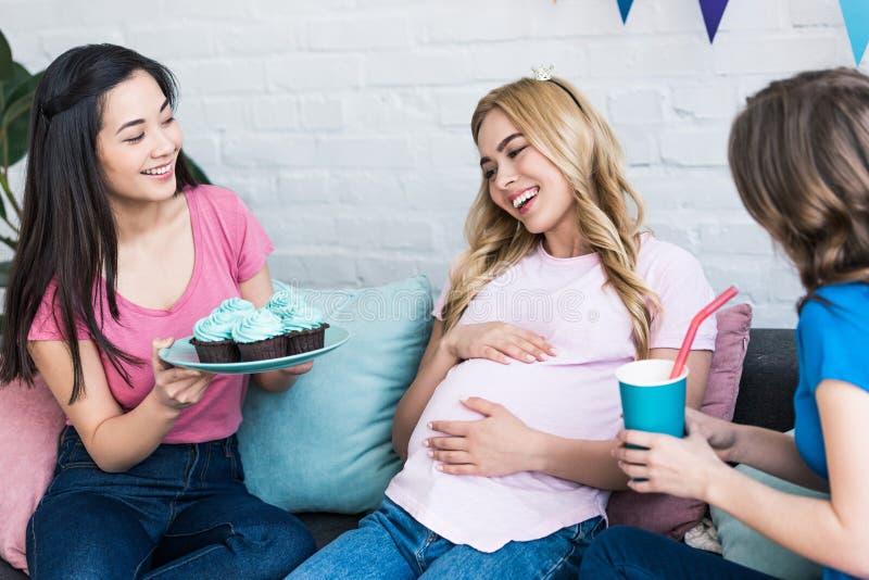 mångkulturella kvinnor som föreslår gravida den vänmuffin och drinken royaltyfri fotografi