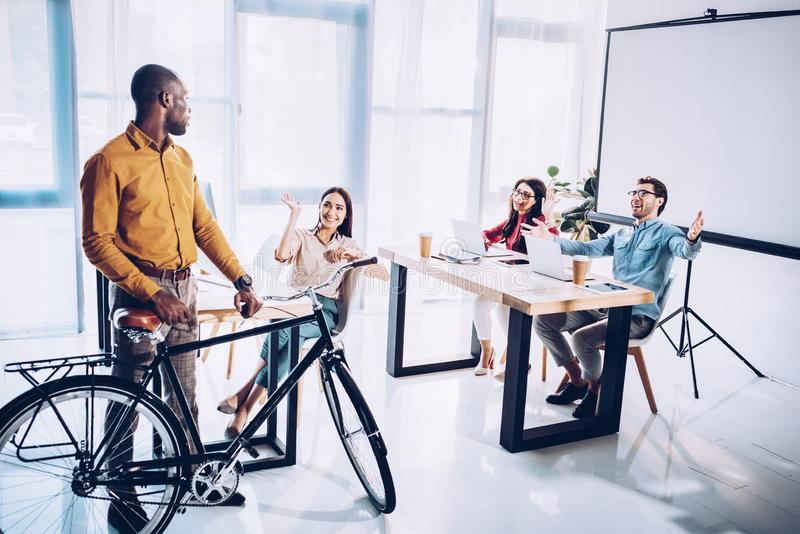 mångkulturellt affärsfolk som hälsar afrikansk amerikankollegan med cykeln arkivfoton