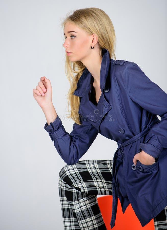 Måste ha begrepp Kvinnamakeupframsida som poserar laget på modern stol Trendigt lag Kläder och tillbehör Blandande stilar arkivbild