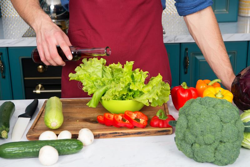 Mått exakt Ingenting havererar maträtten som en dubbel del av vinäger eller olja Händer av manlig hällande grönsallat för kock me royaltyfri fotografi