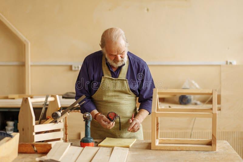 Måttband och handstil för gammal craftsperson hållande något i skrivboken arkivbild