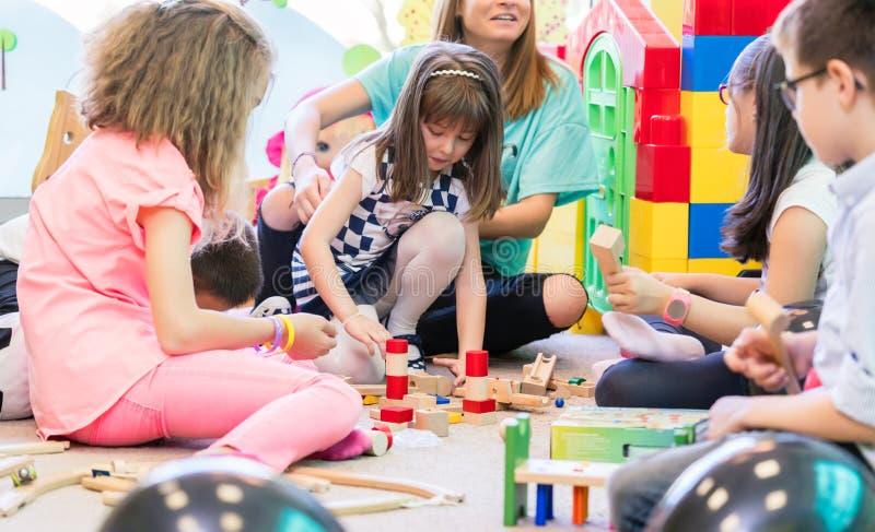 Mæstra d'asilo dedicata che tiene una ragazza timida mentre guardando il gioco di bambini immagine stock libera da diritti