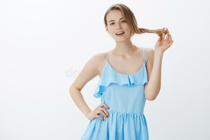 Mèches de roulement de cheveux de femme arrogante belle sûre et élégante sur des doigts tenant des mains sur la taille et posant  photos stock