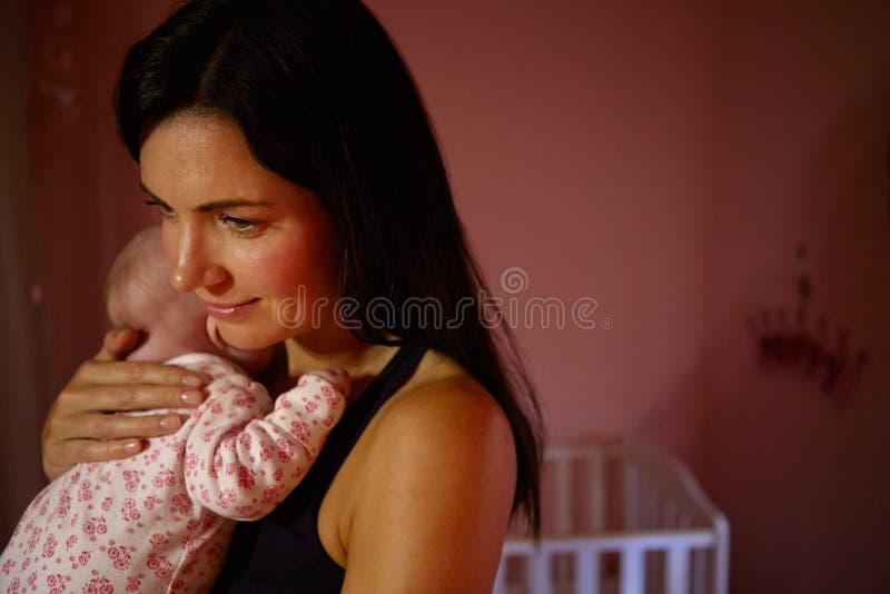 Mère à la maison caressant le bébé nouveau-né dans la crèche photographie stock libre de droits