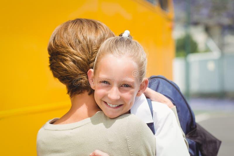 Mère étreignant sa fille en l'autobus scolaire photos libres de droits