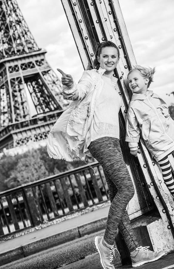Mère active et enfant se dirigeant sur quelque chose près de Tour Eiffel photographie stock