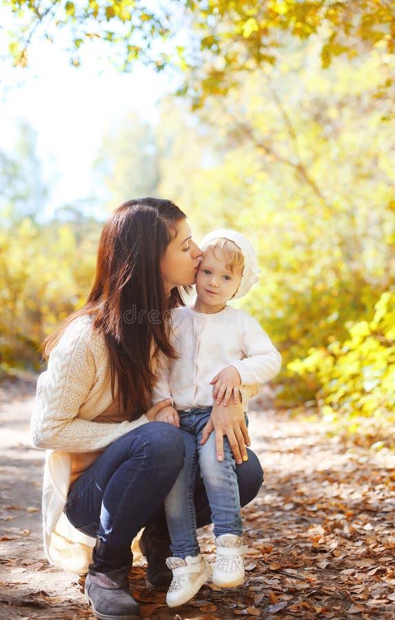 Mère affectueuse heureuse embrassant l'enfant en automne photographie stock