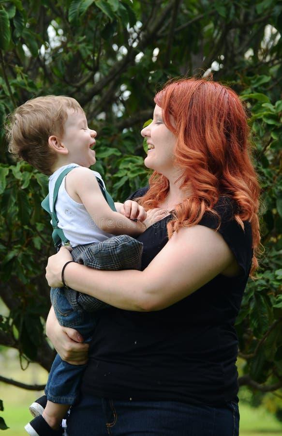 Mère affectueuse tenant le fils de bébé d'enfant en bas âge riant ensemble dehors photo stock