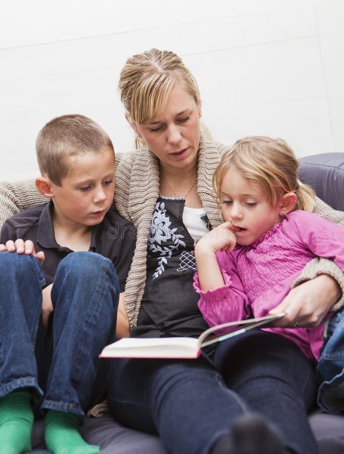 Mère affichant un livre à ses enfants photos stock