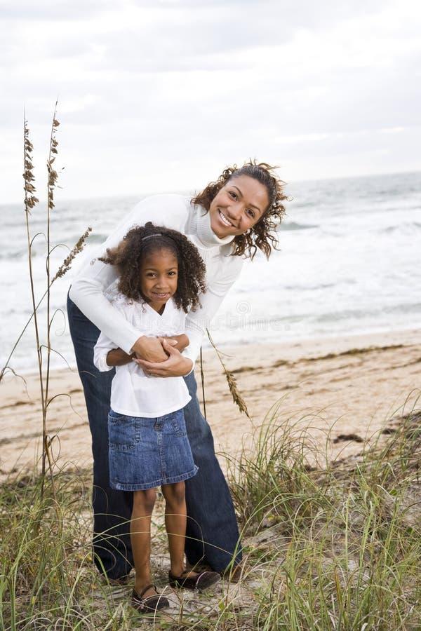 Mère afro-américaine et descendant à la plage photo libre de droits