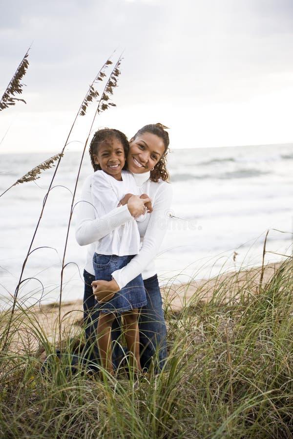Mère afro-américaine et descendant à la plage photo stock