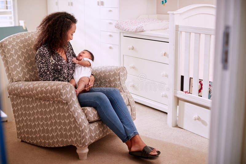 Mère aimante s'asseyant dans le fils de caresse de bébé de chaise dans la crèche à la maison photographie stock