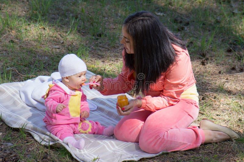Mère alimentant la chéri infantile image stock