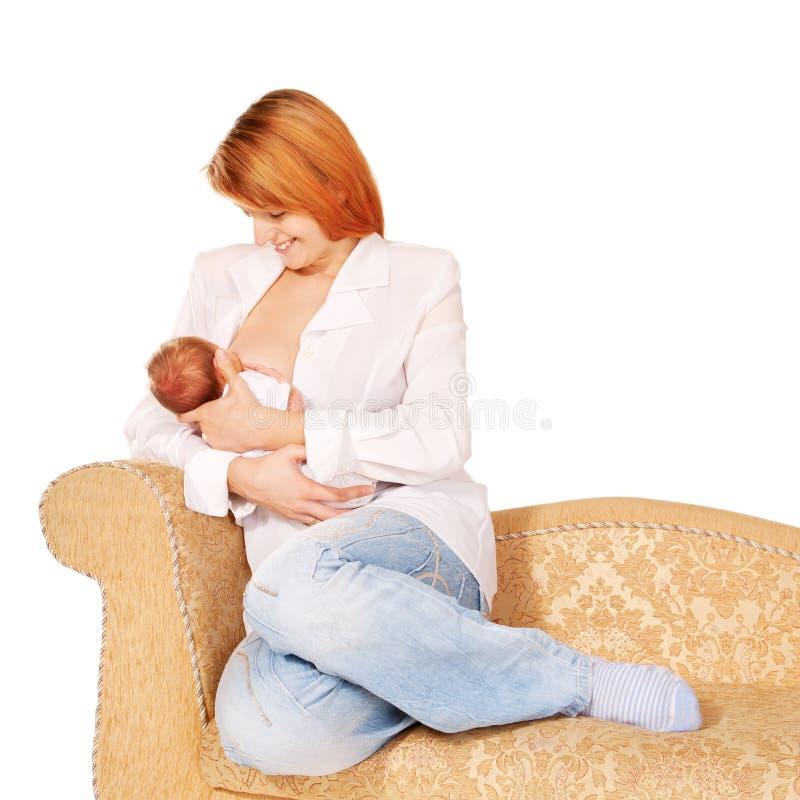 Mère allaitant au sein la chéri nouveau-née sur le sofa photographie stock libre de droits