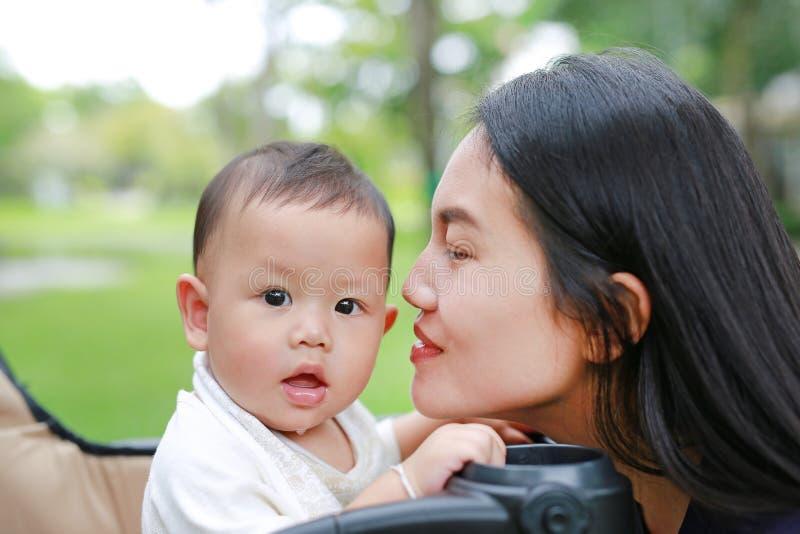 Mère asiatique en gros plan et son bébé garçon sur le chariot en parc photos stock