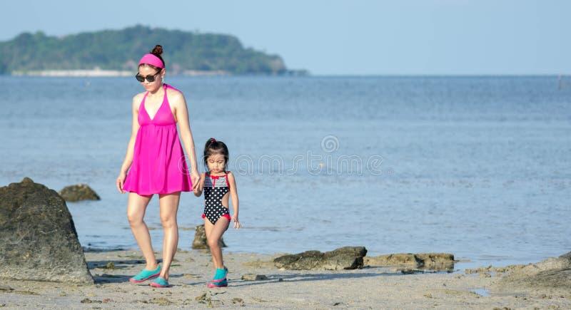Mère asiatique et enfant féminin d'enfant en bas âge tout en marchant dans une station balnéaire images stock