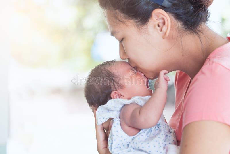 Mère asiatique heureuse étreignant et embrassant son bébé nouveau-né photo libre de droits