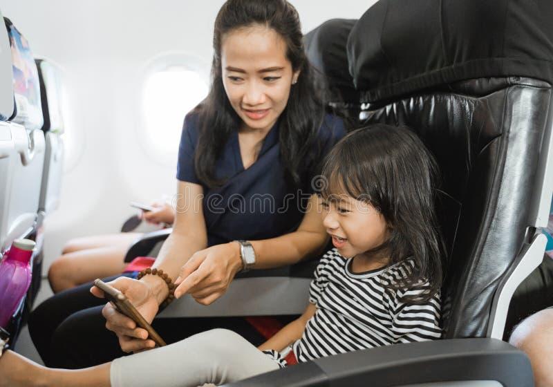 Mère asiatique montrant la photo mignonne à sa fille à l'aide du smartphone images stock