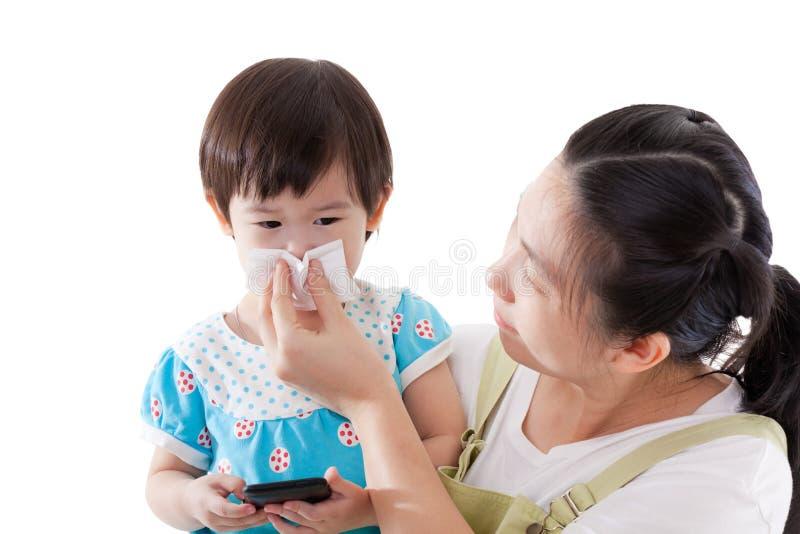 Mère asiatique portant et nez de soufflement sa fille sur le CCB blanc photographie stock