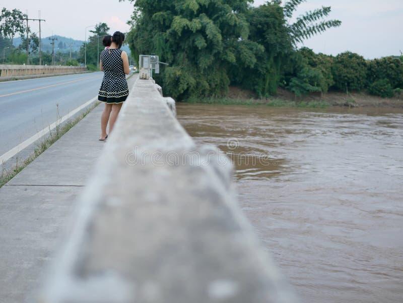 Mère asiatique portant sa petite position de fille sur un pont montrant à son petit bébé une rivière boueuse sombre à l'arrière photographie stock libre de droits