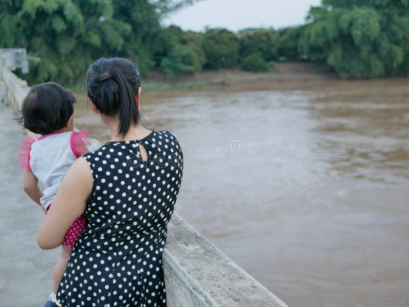 Mère asiatique portant sa petite position de fille sur un pont montrant à son petit bébé une rivière boueuse sombre à l'arrière photo stock