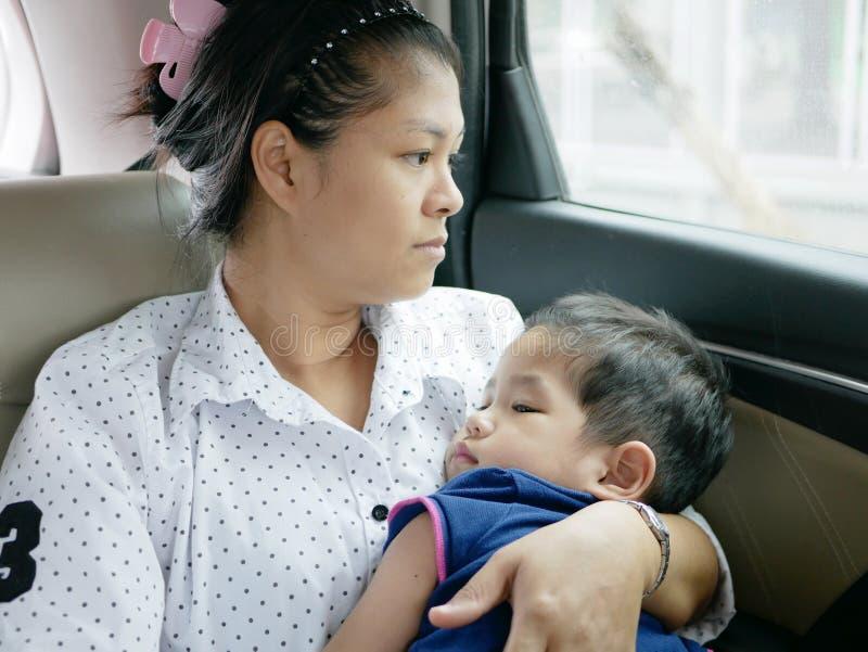 Mère asiatique portant son bébé tout en se reposant dans une voiture mobile sans siège de voiture de bébé photographie stock libre de droits