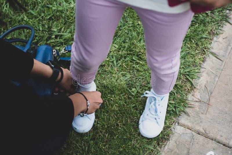 Mère attachant les dentelles de chaussure de l'enfant - utilisation du jour de mère photographie stock