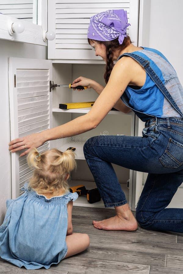 Mère au lieu de père : la petite fille aide la mère à réparer des meubles photo libre de droits