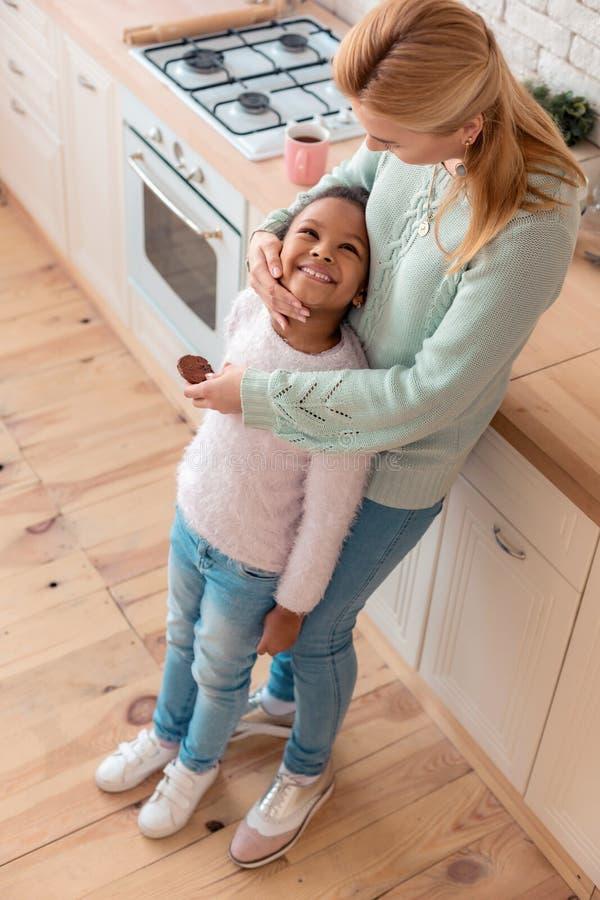 Mère aux cheveux blonds aimante étreignant sa petite fille mignonne photographie stock
