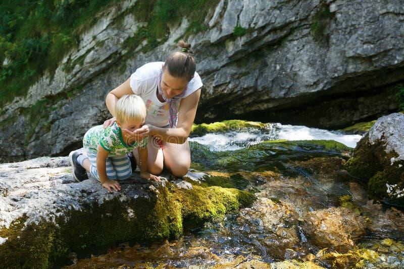 Mère avec de l'eau potable de fils d'un courant pur, frais et frais de montagne en voyage de famille photographie stock