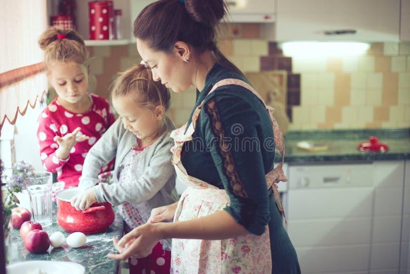 Mère avec des enfants à la cuisine image stock