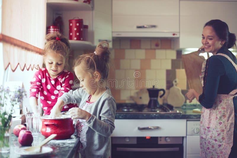 Mère avec des enfants à la cuisine images stock