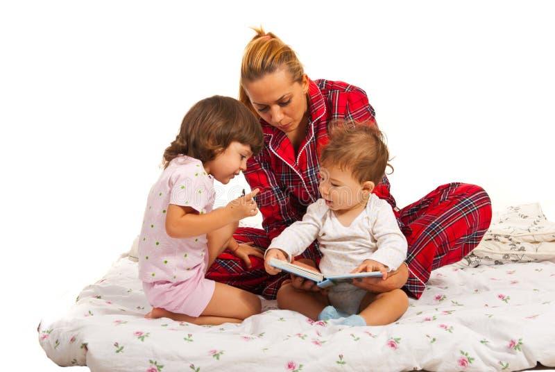 Mère avec des enfants lisant l'histoire photo stock
