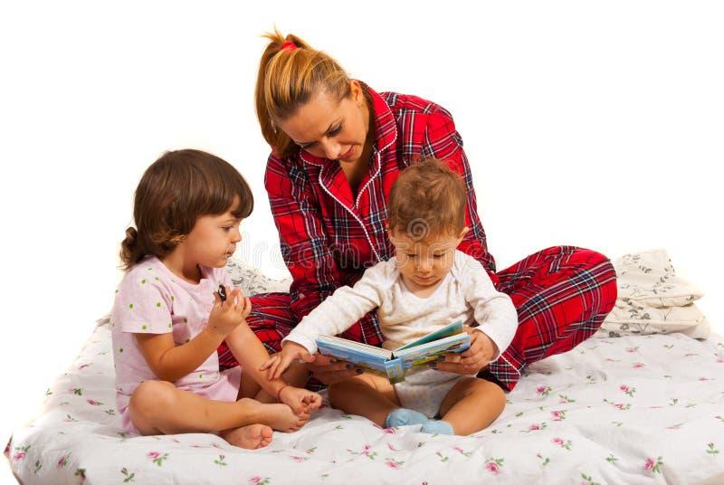 Mère avec des enfants lisant l'histoire photographie stock libre de droits