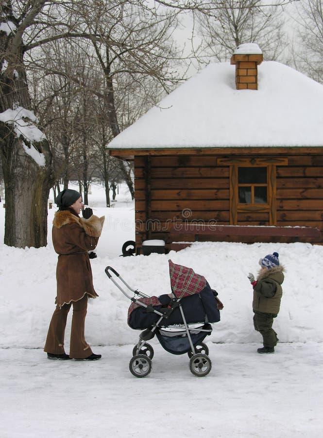 Mère avec des enfants. neige photo stock